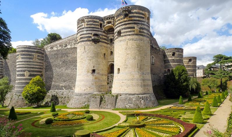 Von außen fast schon etwas bedrohlich und abweisend wirkt das Schloss Angers. Das Schloss liegt direkt über dem Loire-Zufluss Maine in Angers und schaut aus wie eine Mischung aus dem gefürchteten Tower of London und dem berühmten Castel del Monte, welches Friedrich II. im südlichen Italien bauen ließ und welches heute die 1-Cent-Münze Italiens schmückt. (#01)